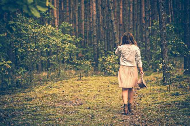 shallow focus photography of woman surrounded by trees
